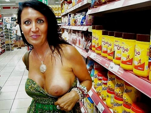 MILF pulling one boob out of her dress in the store