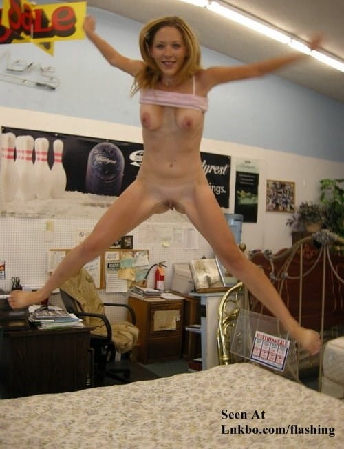 Girl bouncing naked on a bed in a furniture store.