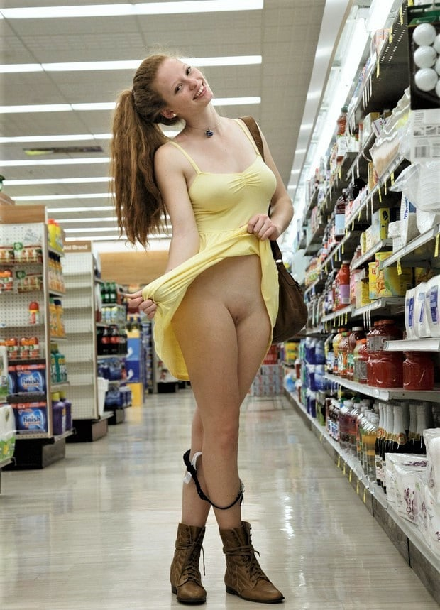 Redhead babe, panties down, flashing her pussy in the store.
